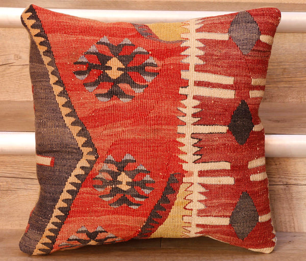 The pieces are often salvaged from old kilim so the pattern or Motifs may be cut in unusual and interesting ways.   This cushion has a geometrical pattern upon it consisting of stylized leaves, bands of interlocking triangles, diamonds and other block patterns in bands.  The colour palette is a red base predominantly with the decoration being in dark brown, yellow and cream with some soft blue highlights.   The back of the cushion is usually Faux suede or cotton.