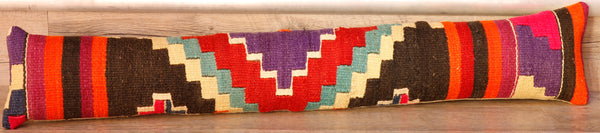 This lovely draught excluder is made from a salvaged piece of Turkish Kilim. It is single-faced with a faux suede/linen backing and fibre filled.  It has bands of pink, purple, orange, and brown on each end, and then a geometric design in the centre containing cream duck egg blue and purple.