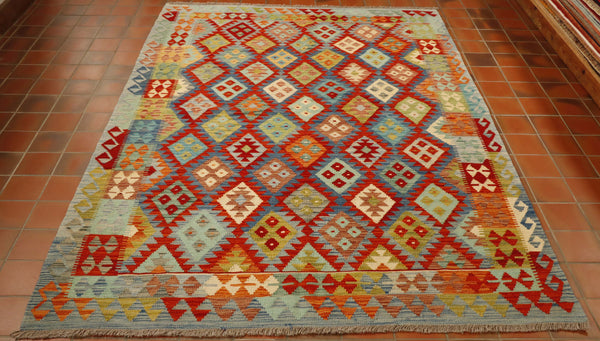 This kilim has a colour palette of various blues (light and dark) duck egg blue, bright terracotta and orange, lime green creams and fawns.  The pattern consists of a series of diamonds symmetrically laid out across the main sections of the rug, each with a contrasting geometric design within.