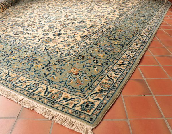 The colour palette used on this Persian Kashan carpet is predominantly cream with a blue green border with dark and light blue picked out the design.