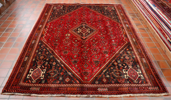This interesting Persian Qashqai rug has been made by nomadic people who live in southern Iran. They tend their own sheep, spin the wool by hand and use natural products for the dyes. The background colour of this rug is a beautiful red with dark brown in the corner sections. There are touches of cream and a little orange to emphasise the design. This piece has on diamond shape medallion in the middle.