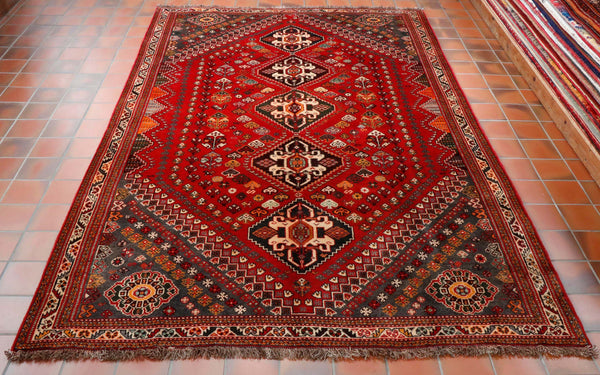 This is a traditional Persian Qashqai tribal  rug made from 100% wool. The design is geometric with 5 diamond shape medallions running through the middle. The central panel has a tomato red background with the corner sections cut off. The corners are a charcoal grey colour. Other colours used in the rug are dark brown, orange, grey and cream.