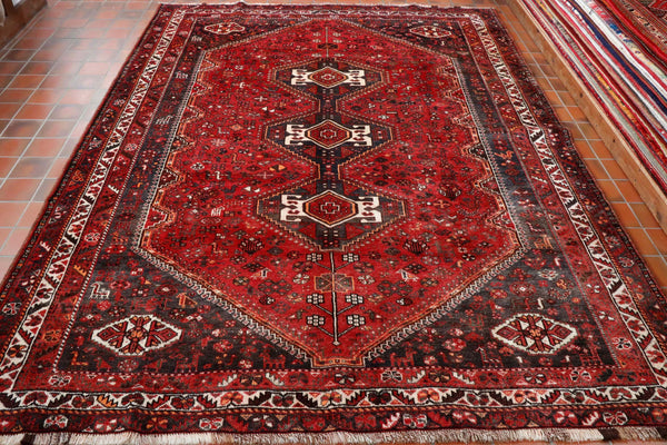 This lovely rich Persian tribal rug is full of warmth and character. It is made from 100% vegetable dyed wool for both the warp and weft and the pile. The background colour is a lively red with a soft charcoal in the four corners and in the three central diamond medallions. Cream, tangerine and brown are the other colours used. This carpet has lots of stylised birds and animals all over it.