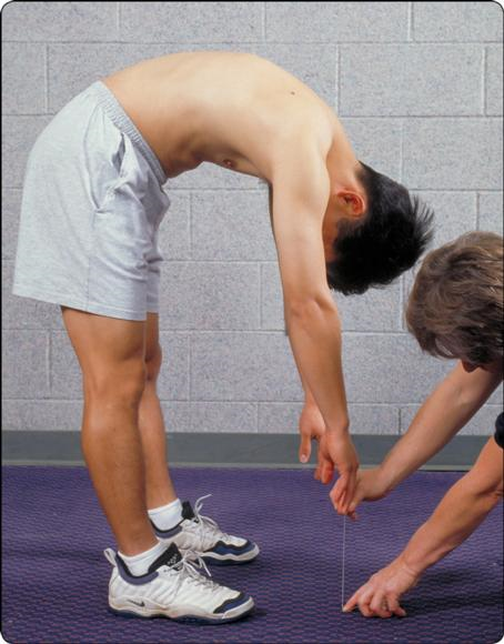 Figure 6.3 Use of a tape measure to examine ROM of the spine. See chapter 11 for details on measurement technique.