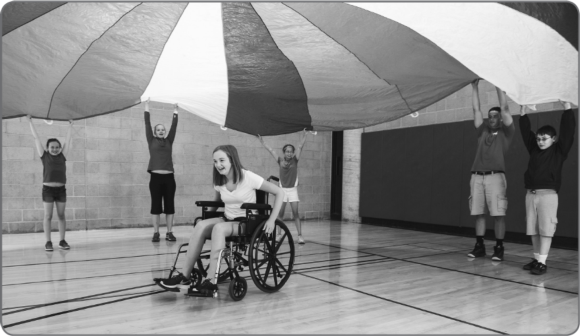 Figure 3.1 As noted in the text, the parachute can be used in inclusive activities in many ways. Here, a student using a wheelchair is easily included.