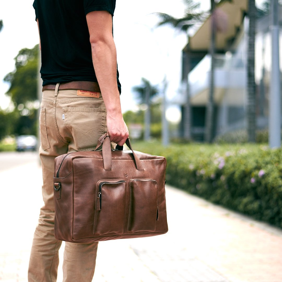 Man holding a brown leather bag. Equz Messenger Bag by Capra Leather.
