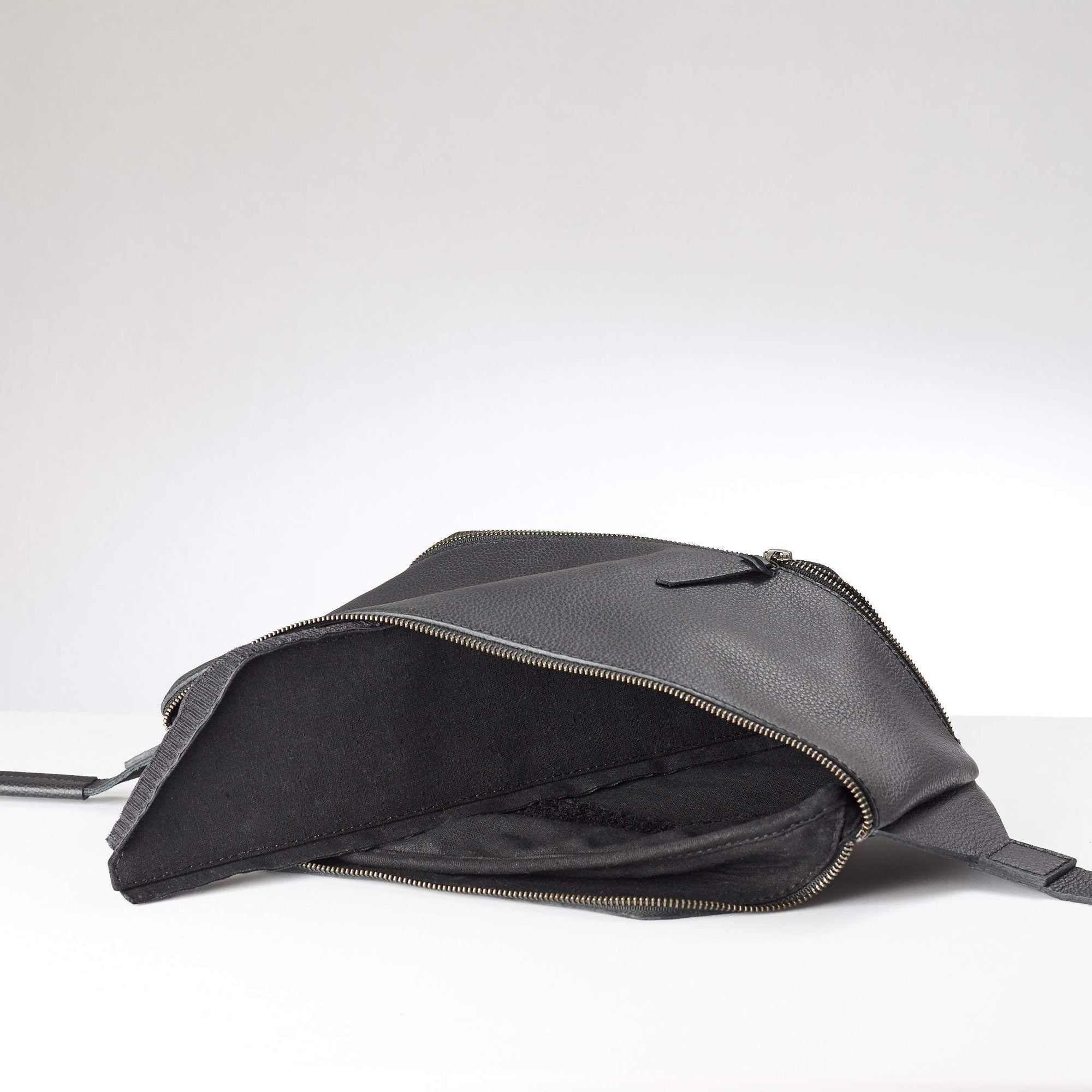 Black Fenek sling bag backpack made by Capra Leather. Frontal view of shoulder bag with single strap.