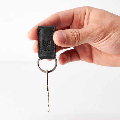 Style photo. Black leather keychain, custom magnetic key fob