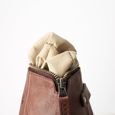 Detail, waterproof interior, hand stitched pull tabs. Brown leather boxer toiletry bag. Mens leather dopp kit travel bag