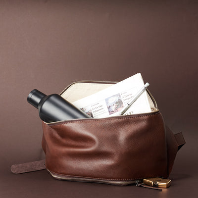 Brown Fenek sling bag backpack made by Capra Leather. Styling of over the shoulder bag with accesory.
