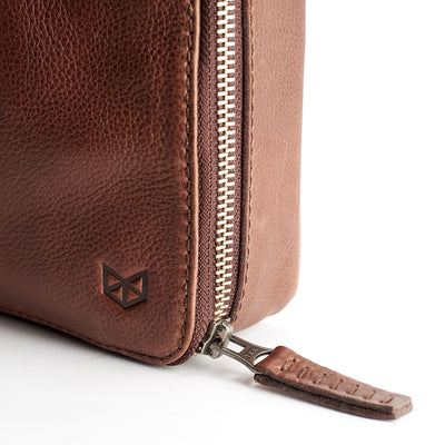 Detail from metallic zipper. Men's brown leather tech 15 inch laptop tablet bag is perfect to travel organized.