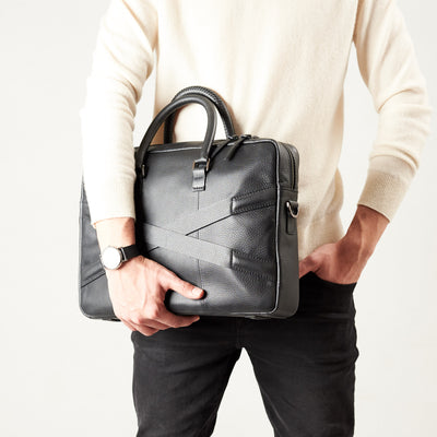 Style model holding crossbody with hands. Black leather briefcase laptop bag for men. Gazeli laptop briefcase by Capra Leather.