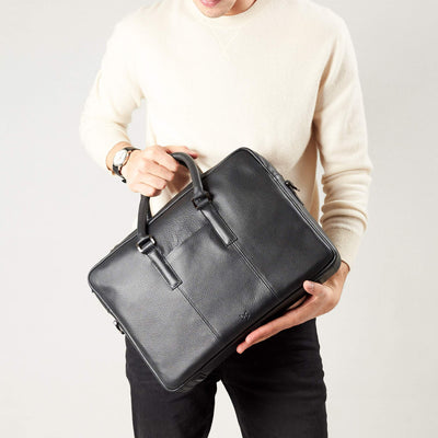 Briefcase with handmade straps in use by model. Black leather briefcase laptop bag for men. Gazeli laptop briefcase by Capra Leather