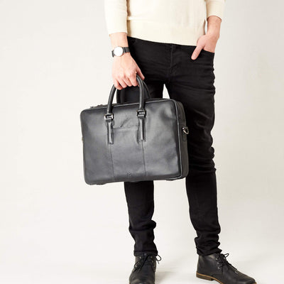 Style view, model holding bussiness document portfolio bag .Black leather briefcase laptop bag for men. Gazeli laptop briefcase by Capra Leather.