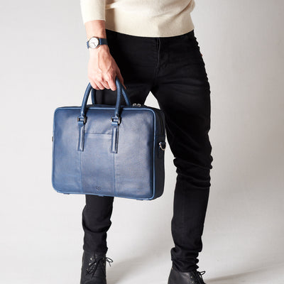 Style view, model holding bussiness document portfolio bag .Blue leather briefcase laptop bag for men. Gazeli laptop briefcase by Capra Leather.