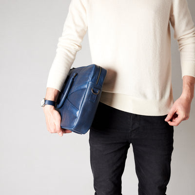 Style model holding crossbody with hands. Blue leather briefcase laptop bag for men. Gazeli laptop briefcase by Capra Leather.