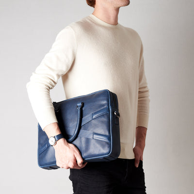 Style side view of model holding workbag. Blue leather briefcase laptop bag for men. Gazeli laptop briefcase by Capra Leather.
