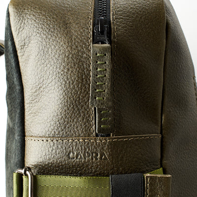 YKK metallic zippers. Green leather backpack with linen interior