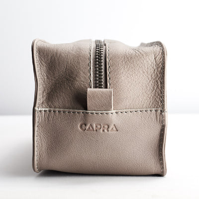 detail. Capra Leather logo engraving. Grey leather barber dopp kit for men