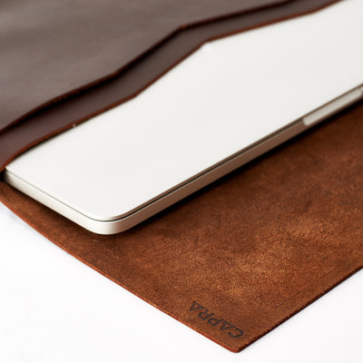 Detail from brown leather sleeve with Macbook pro inside. Notebooks & pens pocket. Mens hand stitched folio