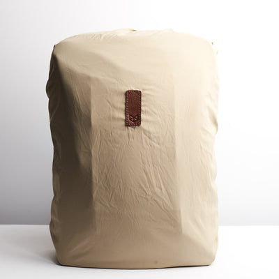 Beige  rain cover for leather backpacks. Mens backpacks accessories