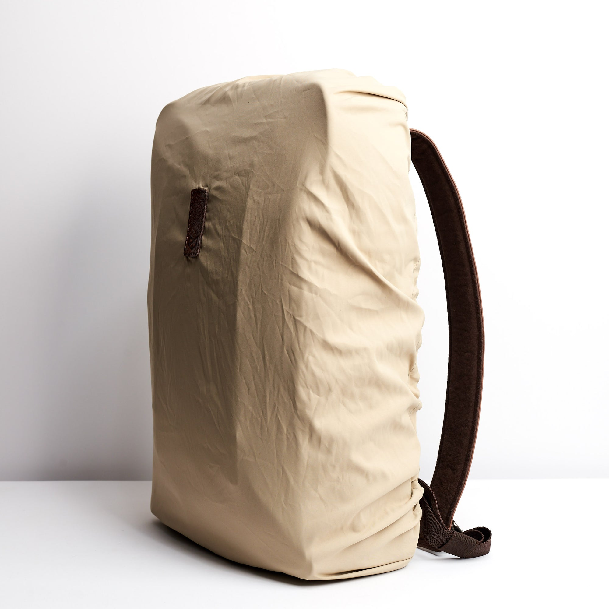 Front Beige Perfect fit for all Capra backpacks. Fashionable matte waterproof material. Leather details by Capra Leather.