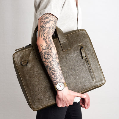 Style holding Roko with hands. Green briefcase by Capra Leather.