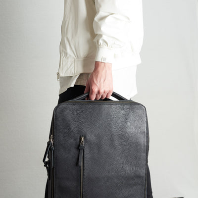 Style one hand holding commuter tech backpack. In black waterproof leather.