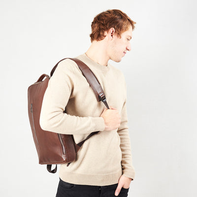 Style slim tech backpack in use. One strap bag holding brown leather handmade essentials bag.