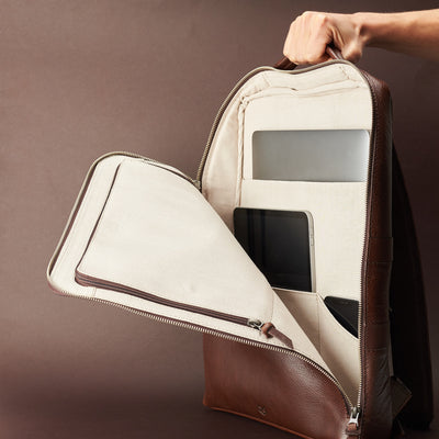 Discreet tech essentials organizer closed and hand holding in brown leather. Everyday use commuter bag by Capra Leather.