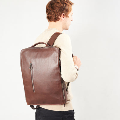 Style slim tech backpack in use back image. One strap bag holding brown leather handmade essentials bag.