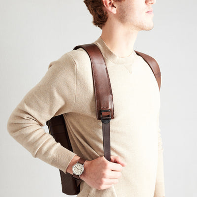 Style slim tech backpack in use side view. One strap bag holding brown leather handmade essentials bag.
