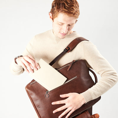 Style slim tech backpack in use back front pocket. One strap bag holding brown leather handmade essentials bag.