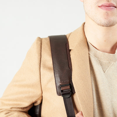 Style slim tech backpack strap detail. One strap bag holding dark brown leather handmade essentials bag.