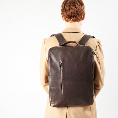 Style slim tech backpack in use back image. One strap bag holding dark brown leather handmade essentials bag.