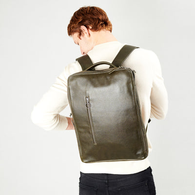 Style slim tech backpack in use. One strap bag holding green leather handmade essentials bag.