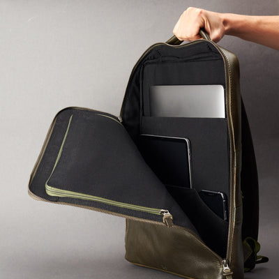 Discreet tech essentials organizer closed and hand holding in green leather. Everyday use commuter bag by Capra Leather.