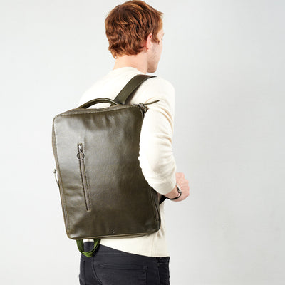 Style slim tech backpack in use back image. One strap bag holding green leather handmade essentials bag.