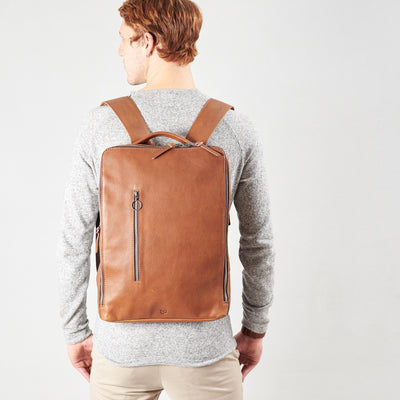 Style slim tech backpack in use back image. One strap bag holding tan leather handmade essentials bag.