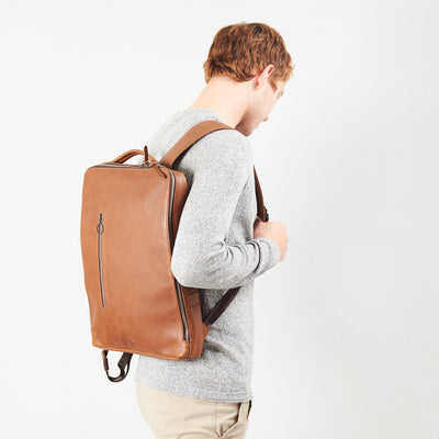 Style slim tech backpack in use. One strap bag holding tan leather handmade essentials bag.