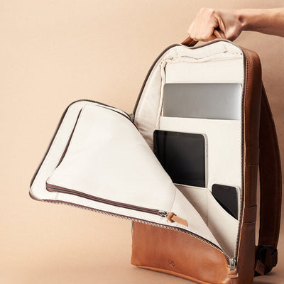 Discreet tech essentials organizer closed and hand holding in tan leather. Everyday use commuter bag by Capra Leather.