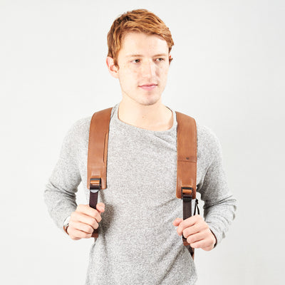 Style slim tech backpack in use. Both straps of bag holding tan leather handmade essentials bag.
