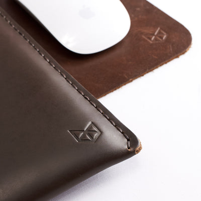 Close up from Capra leather engraved logo. Dark brown leather folio. Macbook Pro full grain leather pouch. Hand stitched mens cases