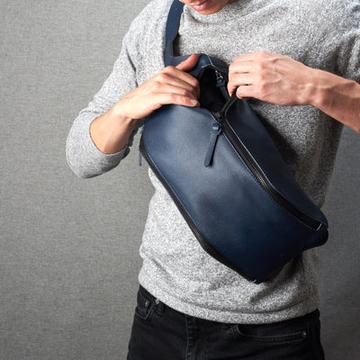 Styling front. Fenek blue sling bag for men by Capra Leather. Urban over the shoulder bag.