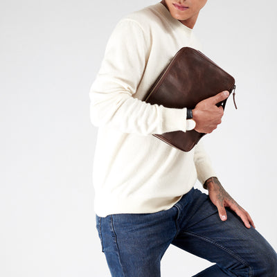 Style picture holding gadget bag in dark brown leather.