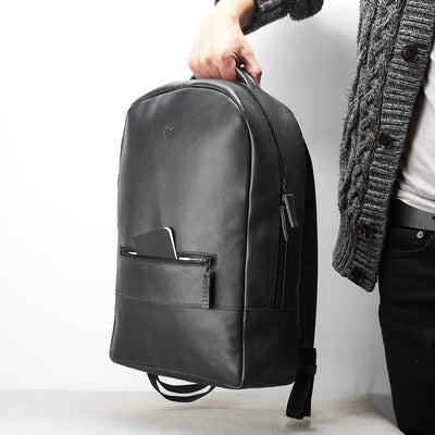 Easy access front pocket. Black leather laptop designer backpack