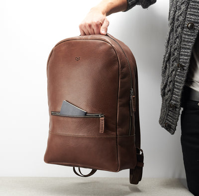 Front essentials pocket. Minimalist brown leather rucksack for men.