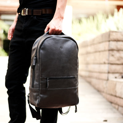 Style photo on street. Black leather rucksack for men