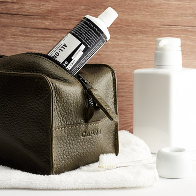Hotel bathroom. Green leather toiletry, shaving bag with hand stitched handle. Groomsmen gifts