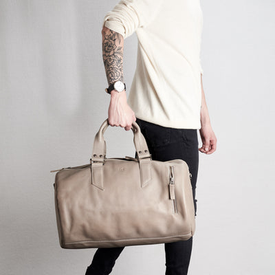 Style handles holding. Substantial grey duffle bag by Capra Leather.